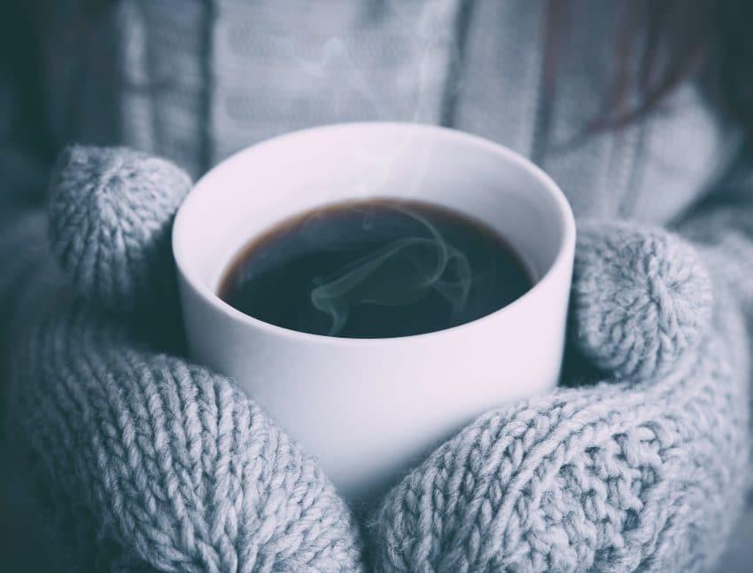 gloved-hands-holding-steaming-mug
